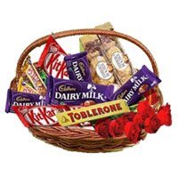Send Birthday Gifts to Ichalkaranji. Basket of Assorted Chocolate and 10 Red Roses and Flowers to Ichalkaranji