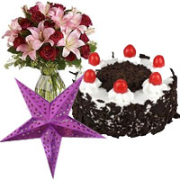 Gifts Delivery in Mumbai. Christmas Star, 1 kg Black Forest Cake, Pink Lily Red Rose Vase 15 Flowers